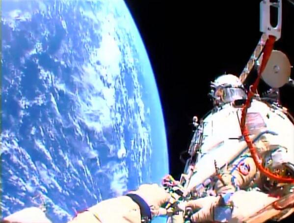Oleg Kotov with the Olympic torch above the planet Earth | via Twitter
